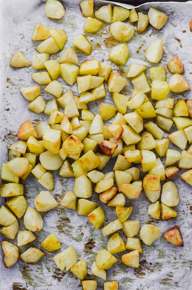 Baked chopped potatoes on a baking sheet ready for patatas bravas
