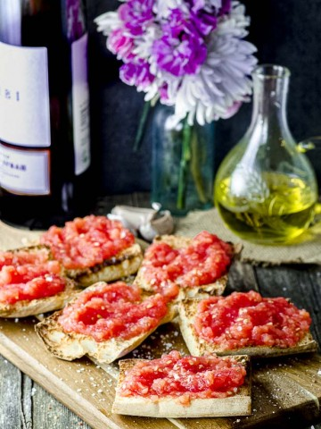 pan con tomate on a wood board with a. bottle of wine and another of olive oil