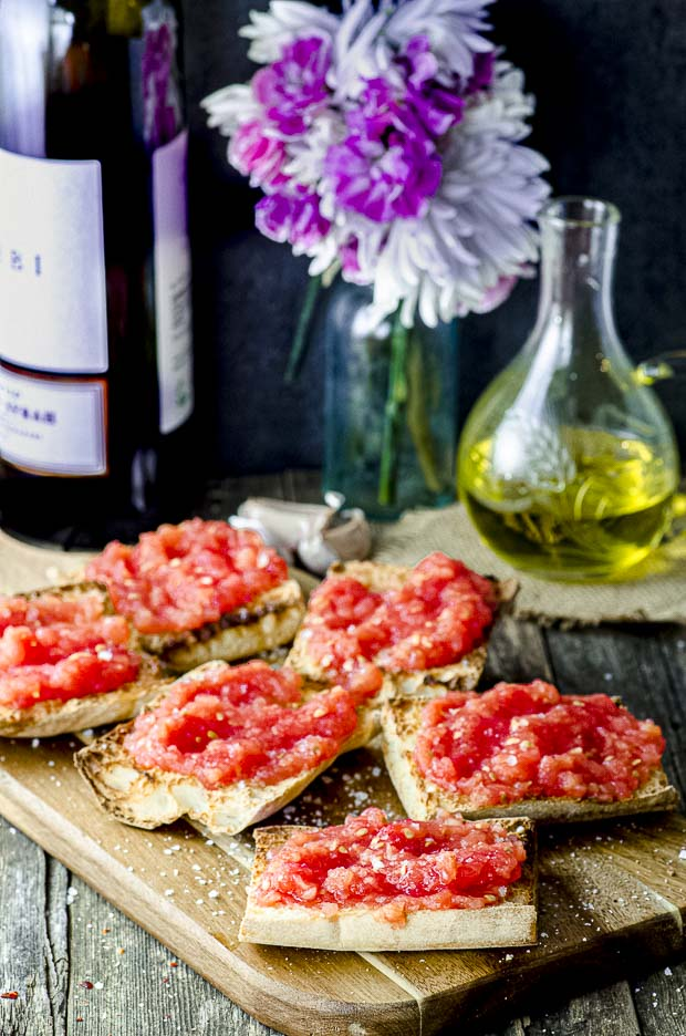 pan con tomate in a wood board with a. bottle of wine and another of olive oil