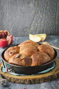 Side view of an apple and honey challah in a round pan