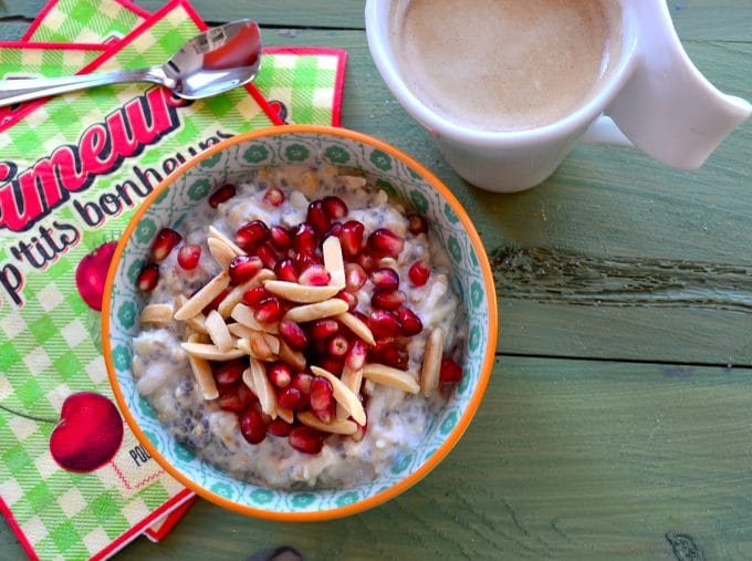 Overhead view of a bowl with overnight oats topped with pomegranates and almonds