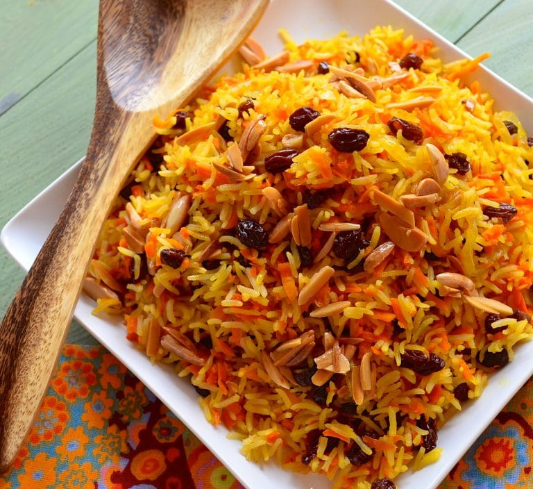 square plate with a mountain of Rosh Hashanah Sweet Basmati Rice with Carrots & Raisins with toasted almonds on top. One wooden spoon on the side of the dish