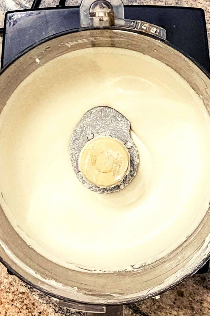 an overhead view of cream cheese and yogurt mixture in a food processor