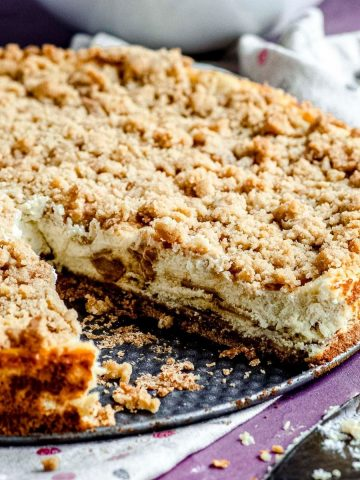 A closer view of apple pie cheesecake with a triangle slice taken