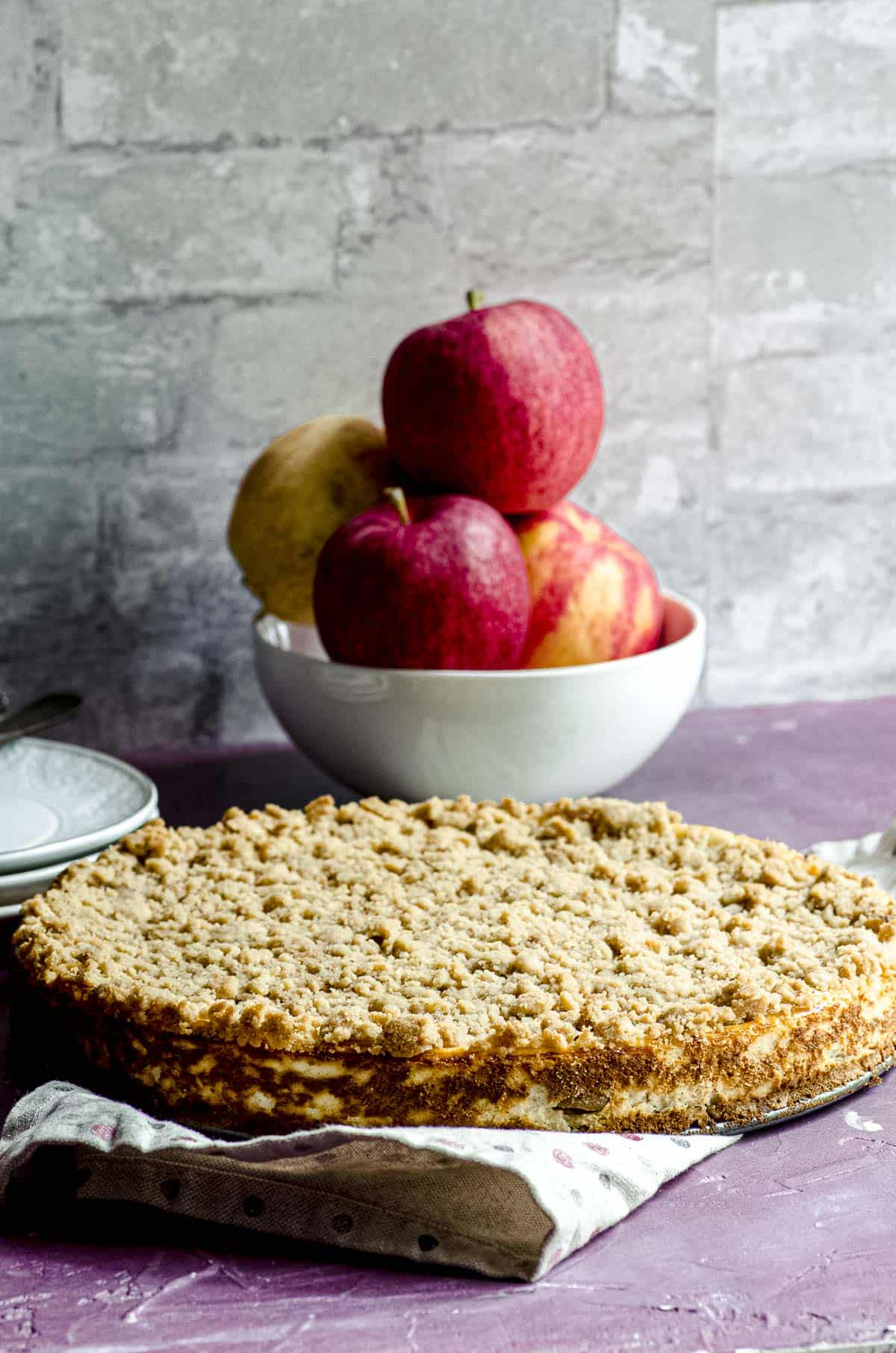 A whole Apple Pie Cheesecake with a bowl with apples stacked up behind it