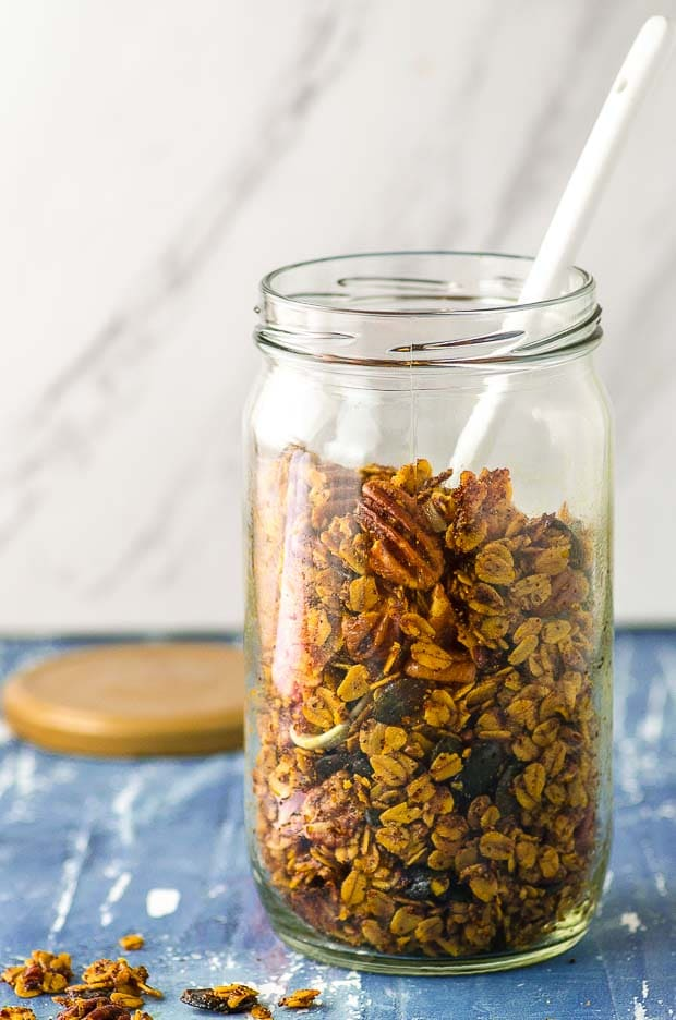 A large glass jar filled savory granola with a white spoon inside the jar
