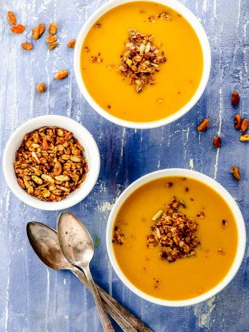 Bird's eye view of two white bowls filled with vegan pumpkin soup and topped with savory granola
