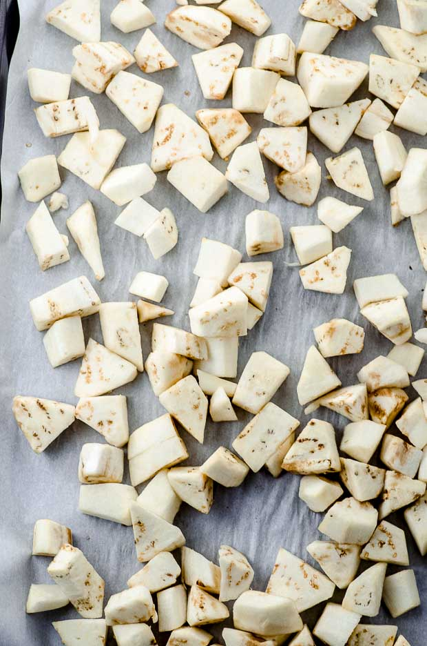 A sheet pan lined with parchment with cubed eggplant