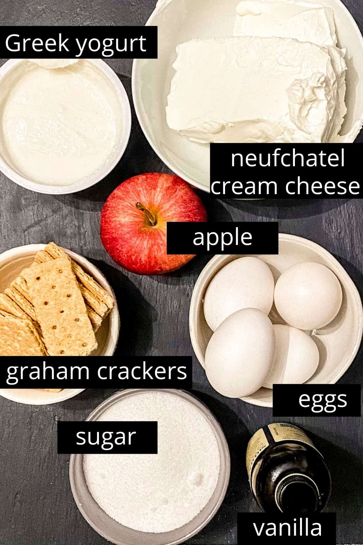 Overhead view of ingredients; greek yogurt, cream cheese, an apple, graham crackers, four eggs, sugar, and vanilla