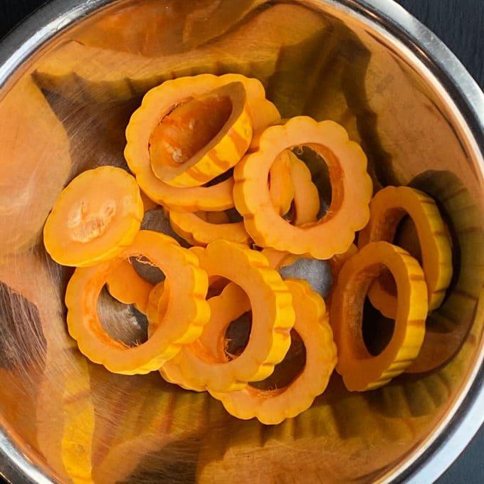 Sliced delicata squash round in a bowl