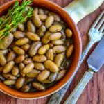 cooked fresh cranberry beans with olive oil and garlic in a glazed terracotta dish with fresh thyme
