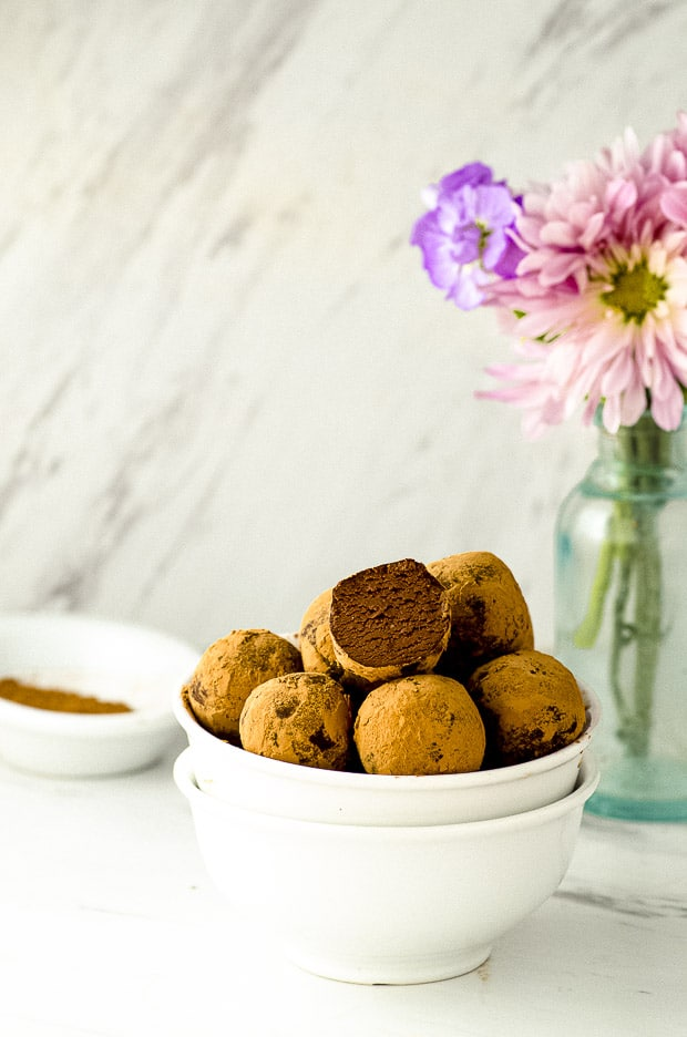Side view of 2 stacked white bowls filled with chocolate truffles