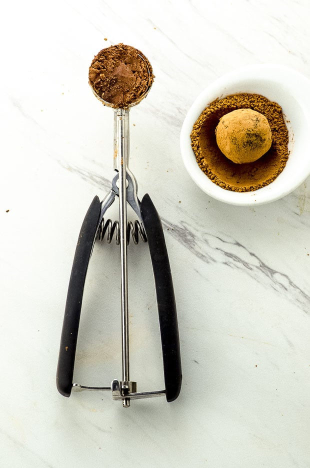 Bird's eye view of an small ice cream scoop with chocolate and a small dish with cocoa power and a chocolate truffle