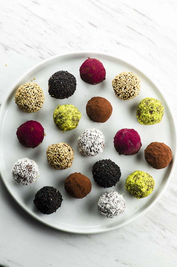 Bird's eye view of chocolate truffles coated with coconut, pistachio, sesame seeds, cocoa powder and beet powder