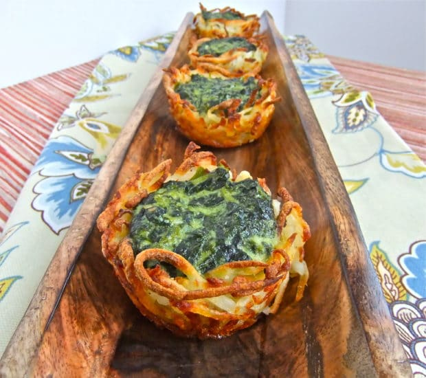 Vegetarian passover recipes: four crispy potato nest filled with a mixture of egg and spinach served on a long narrow wooden plate that had been places on a beige flowered napkin. An award winning recipe.