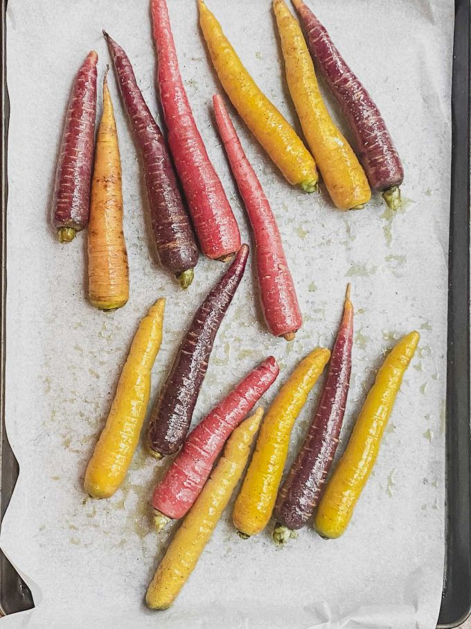 Rainbow carrots on a large baking sheet lined with parchment paper