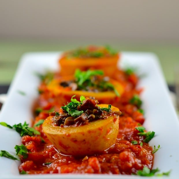 A close up view of a white rectangular plate with mushroom stuffed potatoes on a bed of tomato sauce. One of our vegetarian Passover recipes.