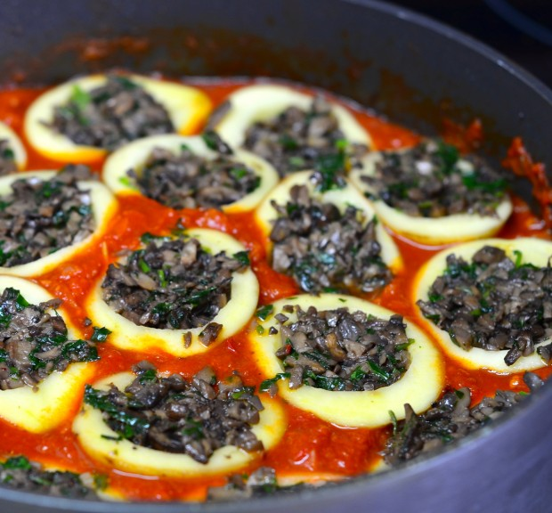 mushroom filled stuffed potatoes in a pan with tomato sauce