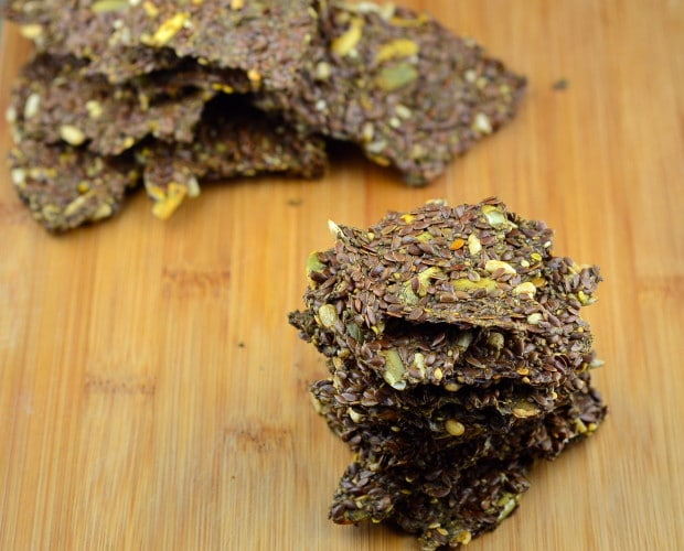 Low Carb Flax and Chia Seed Crackers on a wood surface piled 5-6 crackers high