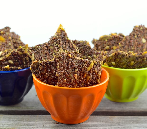 This Low Carb Flax and Chia Seed Crackers in 3 small bowls. The bowls are green, orange and navy blue.
