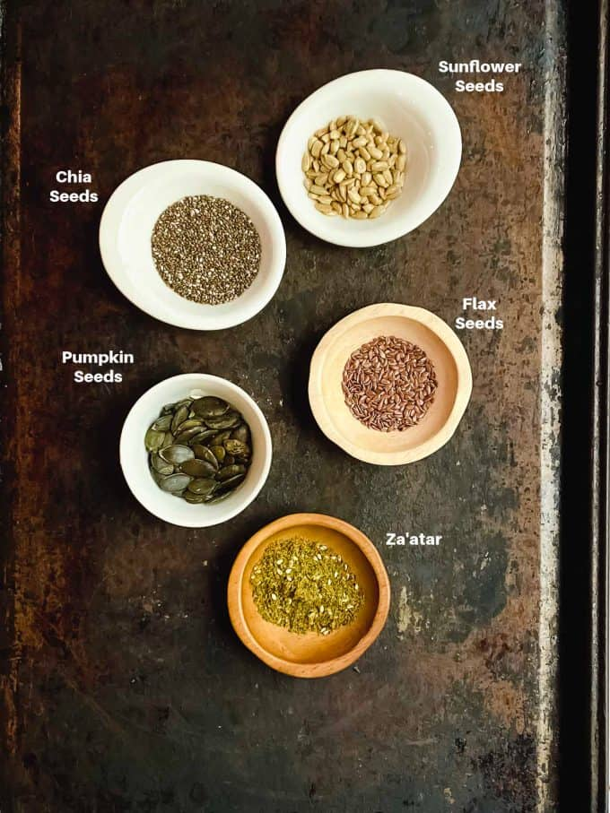 little bowls showing labeled ingredients in flaxseed crackers. Flax seeds, chia seeds, pumpkin seeds, sunflower seeds and za'atar