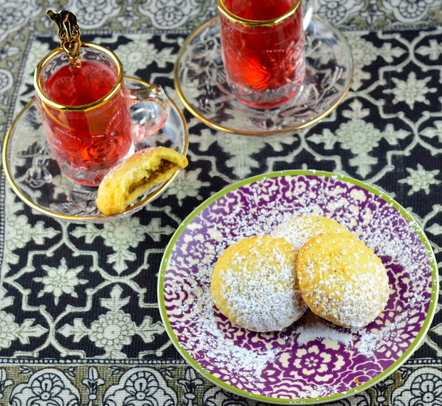 Bird's eye view of a purple printed plate with 2 full maamoul. Next to the plate there are two glasses of tea.