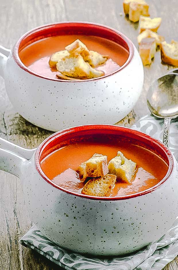 2 bowls of gazpacho topped with toasted croutons