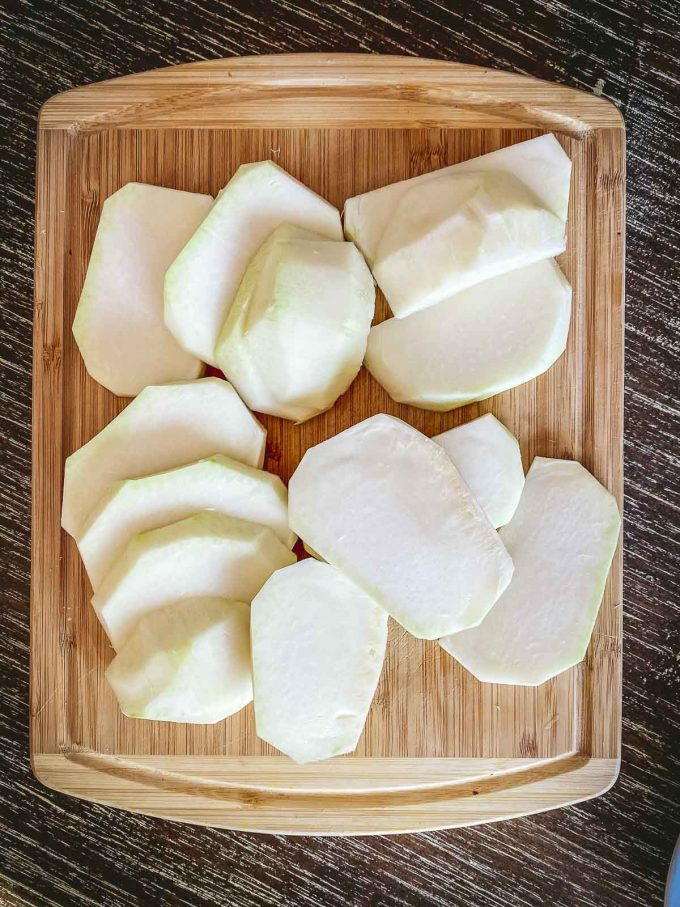 Two peeled kohlrabi bulbs sliced into rounds on a wood cutting board