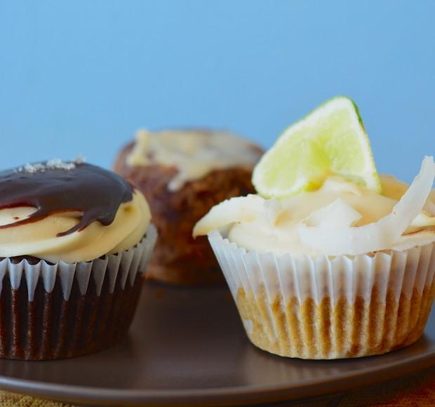 Salted caramel & coconut lime cupcake. Cinnamon bun on the background