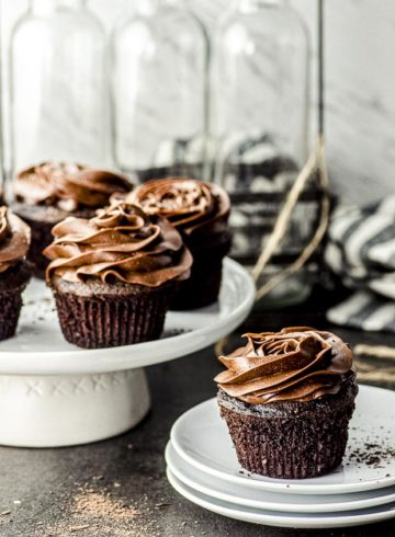 Side view of four chocolate cupcakes with chocolate frosting on a white cake stand and one chocolate cupcake on a stack of white plates