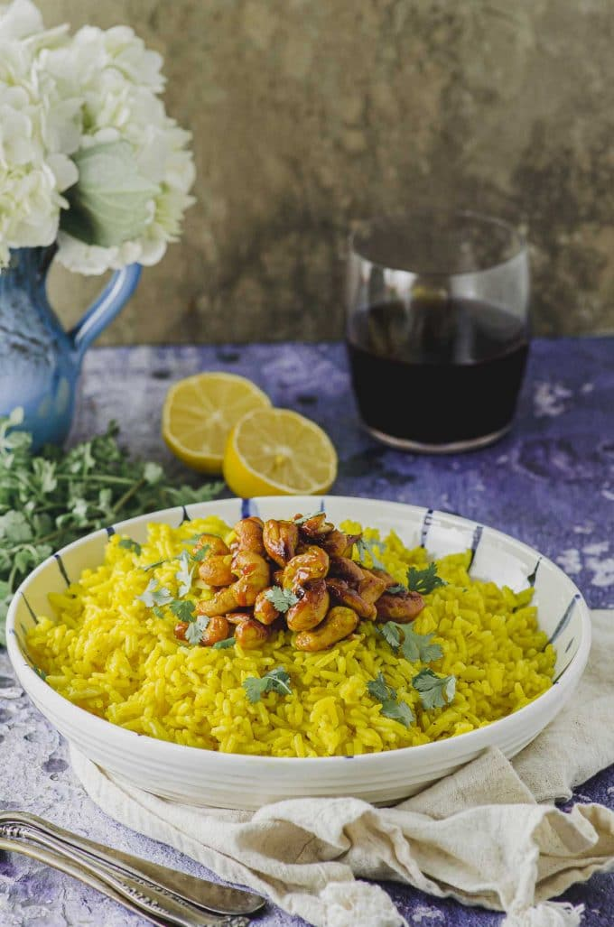 Sideview of a large bowl filled with yellow turmeric rice topped with spiced cashews