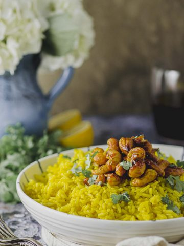 partial side view of a white bowl filled with turmeric rice and topped with spiced turmeric cashews