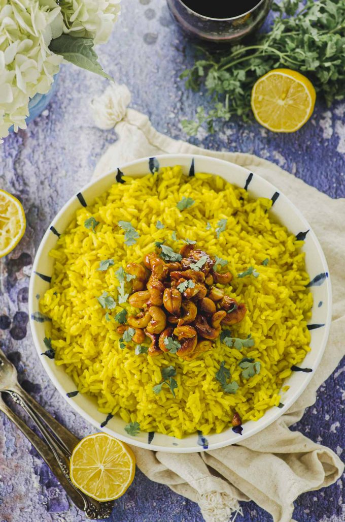 Overhead view of a white plate filled with yellow turmeric jasmine rice topped with spiced cashews