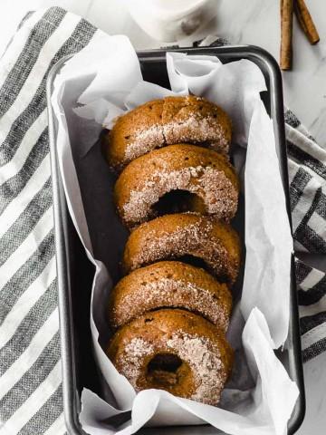 5 apple cinnamon donuts lined in a metal pan