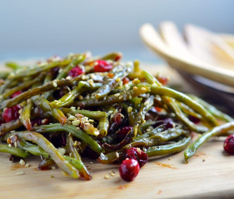 A pile of roasted green beans with cranberries and Dukkah on a wood board