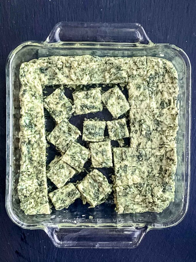Cutting squares of spinach semolina gnocchi in a square glass baking dish