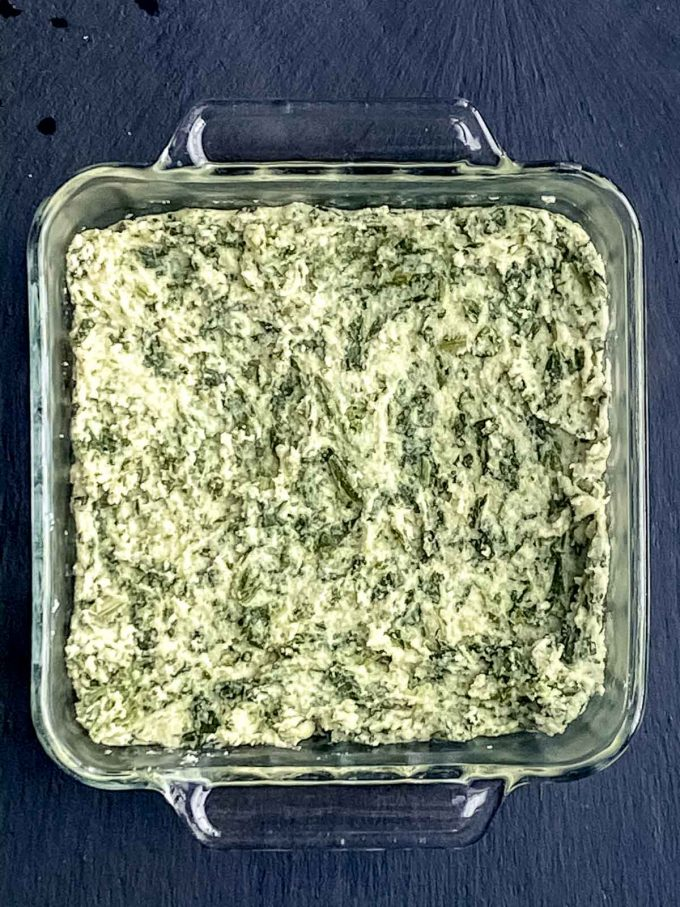 A square glass baking dish with spinach semolina gnocchi dough