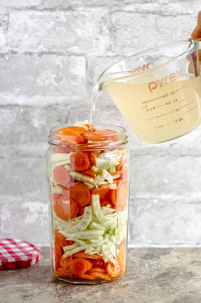 pouring pickling liquid on top of a jar of sliced carrots and fennel