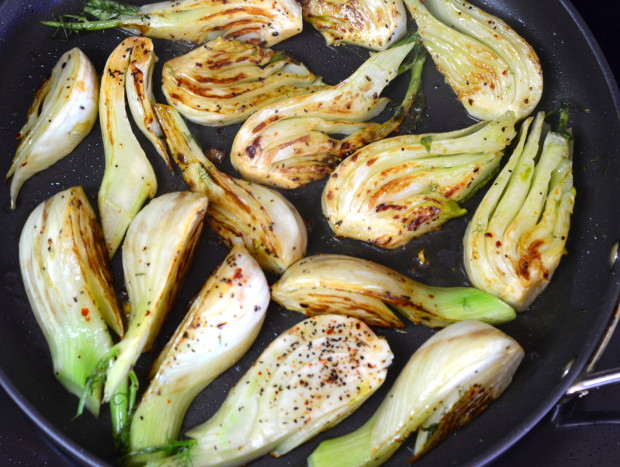 Close up of caramelized fennel quarters in a skillet