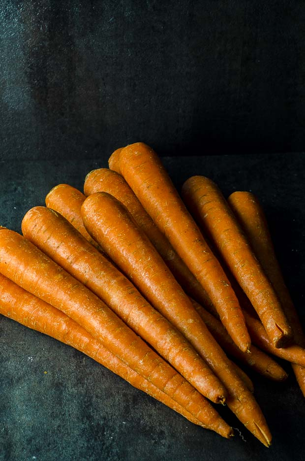 A pile of carrots on a black surface