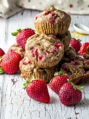 Five Vegan Pan Roasted Strawberry & Fig Breakfast Muffins piled up on a white wood surface. around the muffins there are fresh strawberries and in the background there is a beige napkin with pink, red and white polka dots