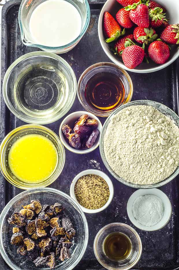 bird's eye view of all the ingredients required to make the Vegan Pan Roasted Strawberry & Fig Breakfast Muffins. splelt flour, almond milk, ground flax seeds, orange juice , dates, dried figs, maple syrup, baking powder, coconut oil