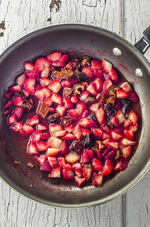 A pan with strawberries, dates and orange juice cooking to make Vegan Pan Roasted Strawberry & Fig Breakfast Muffins.