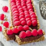 Up close view of chocolate tart covered in fresh raspberries