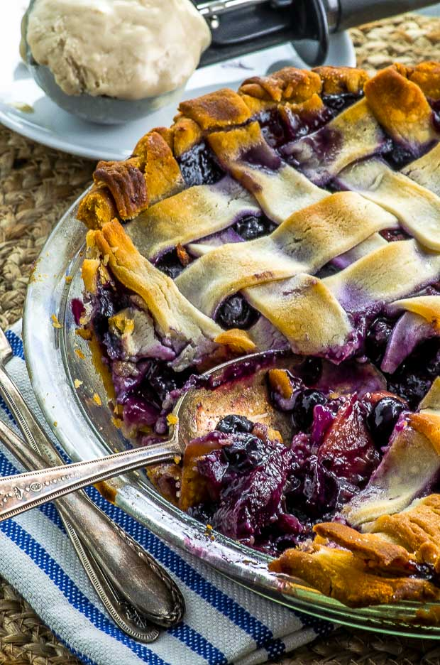 taking a slice of Peach Blueberry Pie with a spoon and some ice cream on the background