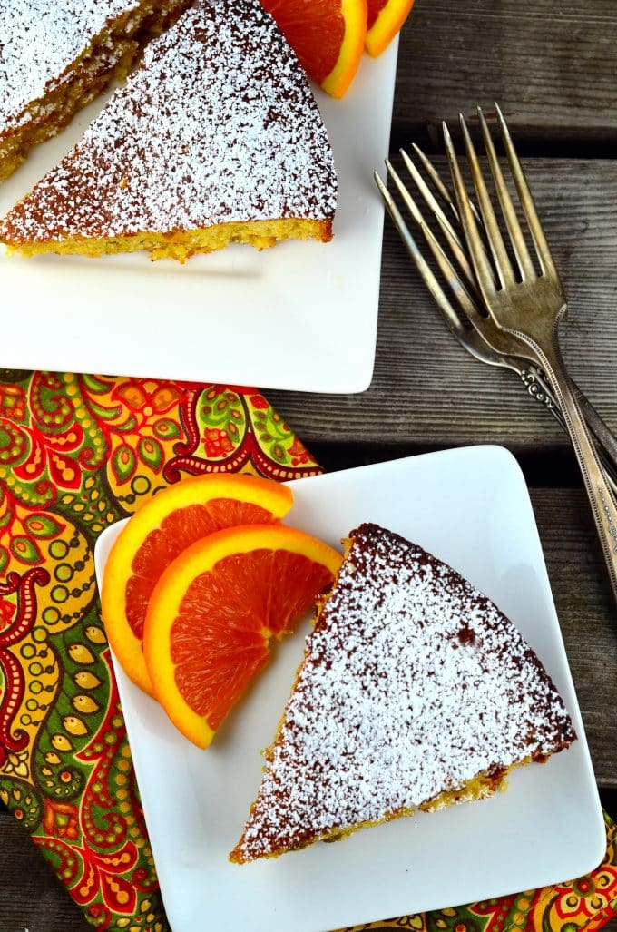 Birds eye view of side view of 2 white square plates with a slice of orange honey almond cake and 2 sliced of fresh orange on each plate. There is a printed orange and green napkin under the plates.