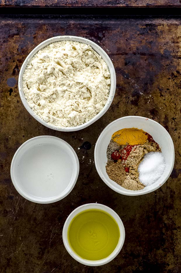 Bird's eye view of 4 bowls with ingredients for gluten-free falafel crackers