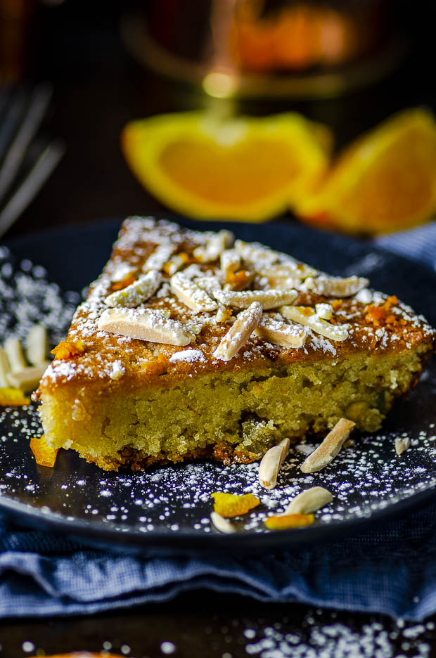 Side view of a slice of Honey Orange Almond Cake on a black plate. One of our vegetarian Passover recipes.