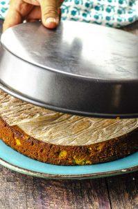 """taking the Orange Honey Almond Cake out of an 8"""" round baking pan"""