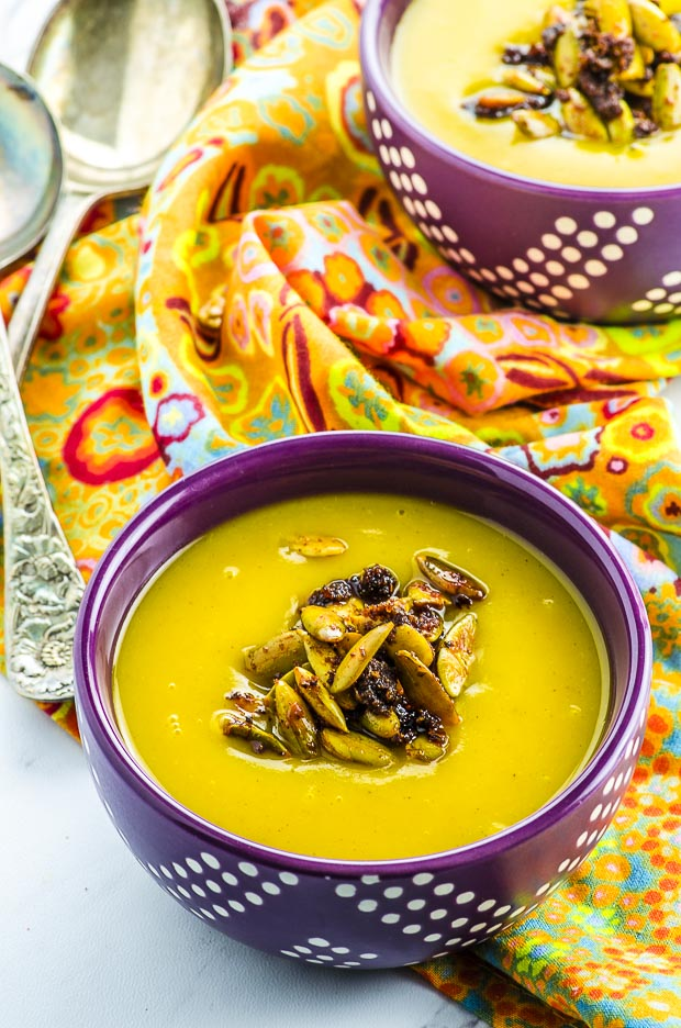 Two purple and white polkadot bowls filled with roasted butternut squash soup, topped with spiced pumpkin seeds, on a printed orange, blue and red napkin